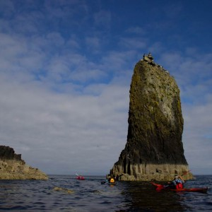 Sea kayaking past a sea stack off the Isle of Canna,