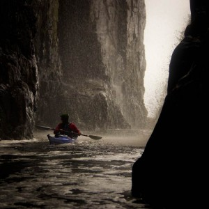 Sea kayaking into a sea cave on the East coast of Rum.