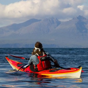 Sea kayaking off the north end of Rum with the black Cuillin and the isle of Skye beyond.