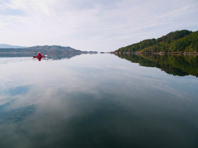 A sea kayaker in Loch Moidart, paddling past Eilean Shona.